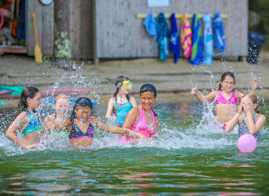 girls at summer camp splashing in water at lake