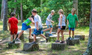 sumemr camp kids walking on tree stumps