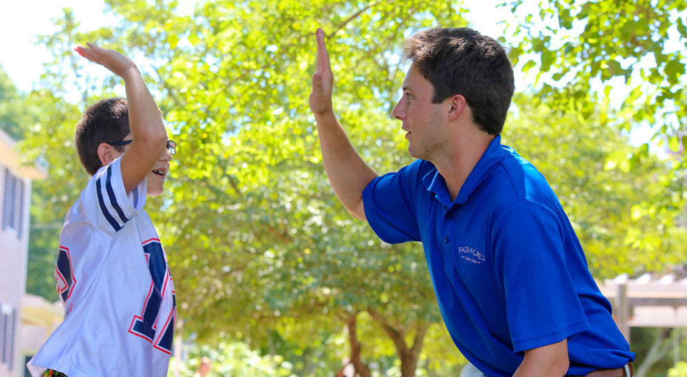 summer camp staff memeber and boy hi five