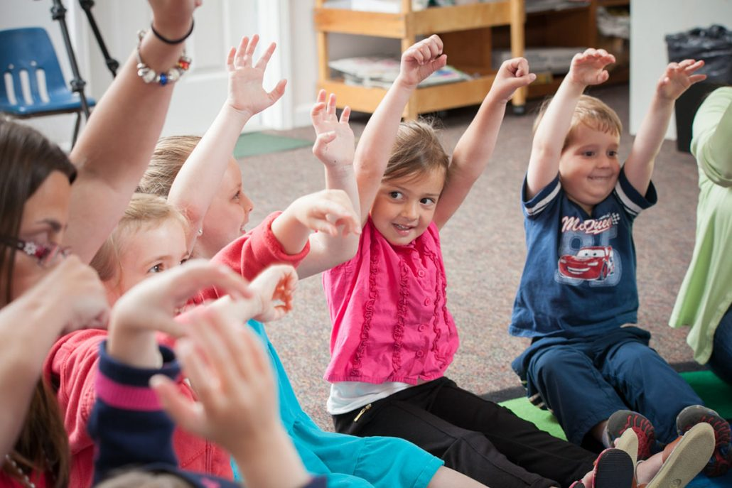 young students raising hands in circle at school