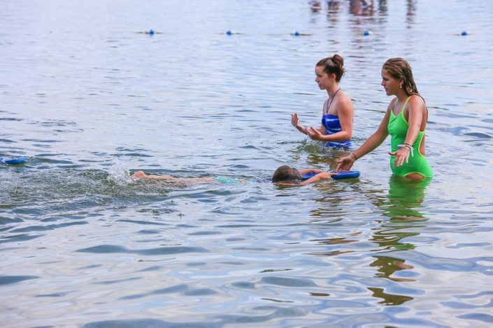 two female camp staff members teaching girl how to swim